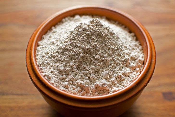 Diatomaceous Earth in an earthenware bowl against a wooden background