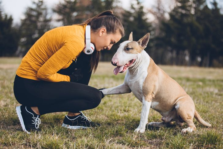 Woman doing exercises outdoors with her dog