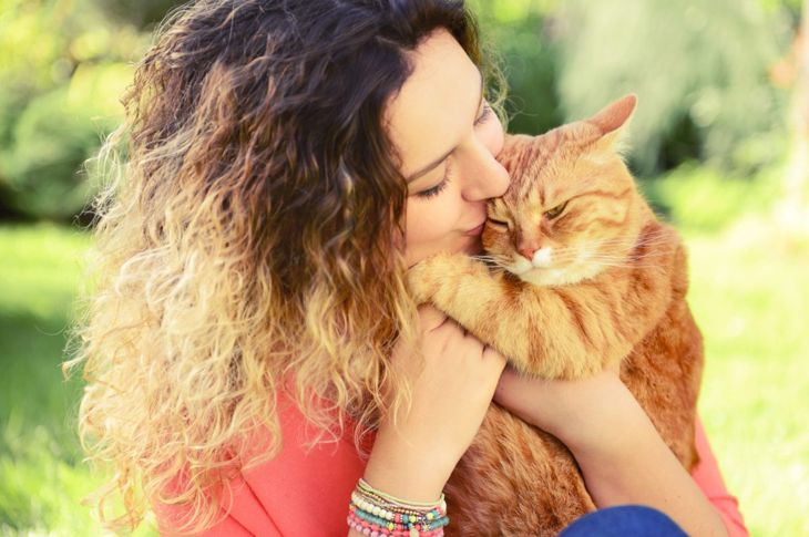 Woman loves cat gives kiss