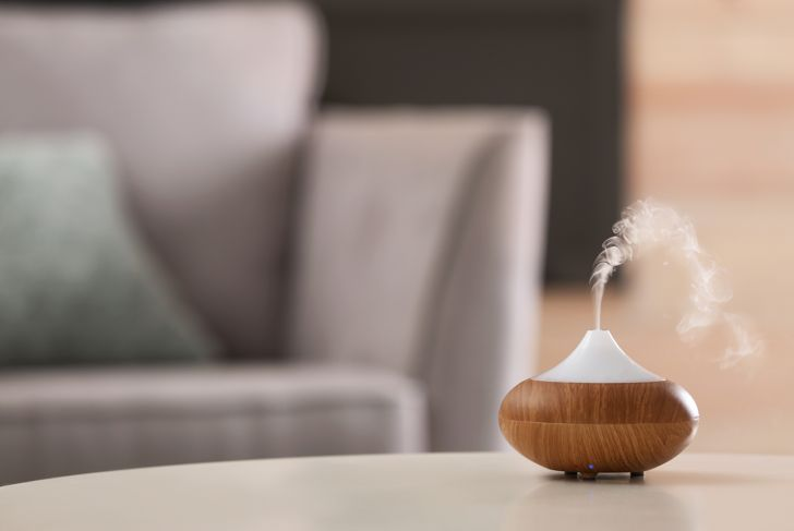 Aroma oil diffuser lamp on table against blurred background